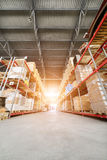 Long shelves with a variety of boxes and containers. Large industrial warehouse. Long shelves with a variety of boxes and containers. Bright sunlight Royalty Free Stock Photos