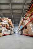 Long shelves with a variety of boxes and containers. Warehouse industrial and logistics companies. Long shelves with a variety of boxes and containers Royalty Free Stock Photography
