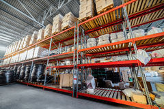 Long shelves with a variety of boxes and containers. Warehouse industrial and logistics companies. Commercial warehouse. Boxes and crates stocked on the shelves Stock Images