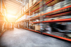 Long shelves with a variety of boxes and containers. Warehouse industrial and logistics companies. The boxes on high shelves stocked. Motion blur effect. Bright Stock Photos
