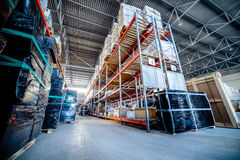 Long shelves with a variety of boxes and containers. Warehouse industrial and logistics companies. Long shelves with a variety of boxes and containers. Toning Stock Image