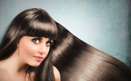 Long shiny hair of a beautiful brunette. Woman Stock Photo