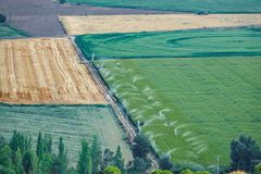 Agriculture fields with irrigation machines working. Long shot of agriculture fields with irrigation machines working Royalty Free Stock Image