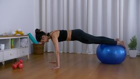Attractive Indian sportswoman demonstrating exercises using a gym/fitness ball