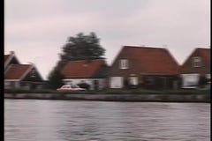 Long shot car driving along side river stock video