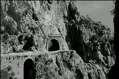 Long shot car driving out of mountain tunnel stock footage