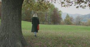 Long shot. Caucasian blond woman slomo walking toward fall woods touching tree. Following behind gimbal.Storytelling stock video