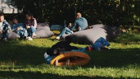 Long shot of Children playing with inflatable tube during outdoor event in park. Group of young people relaxing on bean bags on backround stock footage