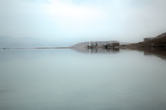 Hotels at Dead Sea Shoreline. Long shot of the Dead Sea on a hazy morning, with a group of hotels at its shore Royalty Free Stock Image