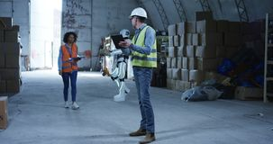 Engineers talking while robot works in the background. Long shot of engineers talking while robot works in the background stock video