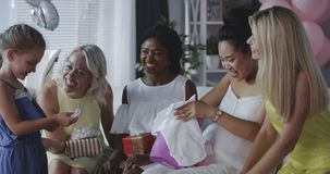 Friends celebrating young mother. Long shot of friends celebrating young mother with gifts stock video