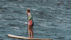 Long shot of girl in full swimsuit shaky rides a surfboard using paddle. On a windy day stock video