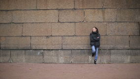 Long shot of the girl near the stone wall of Peterhof stock video footage