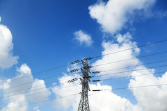 Electricity Pylon & Cloudy Sky. Long shot of a high-voltage electricity pylon and power lines, on the background of the blue & white cloudy sky Royalty Free Stock Image