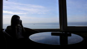Long shot of silhouette of young beautiful girl. Silhouette of young beautiful woman sits in a cafe with panoramic views of atlantic ocean. Morning with a cup of stock video