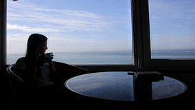 Long shot of silhouette of young beautiful girl. Silhouette of young beautiful woman sits in a cafe with panoramic views of atlantic ocean. Morning with a cup of stock footage