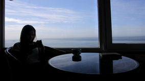 Long shot of silhouette of young girl sits in a. Silhouette of young woman sits in a cafe with beautiful panoramic views of sean. Morning with a cup of coffe stock video footage