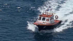 Long Shot of a Small Pilot Boat in Sea. A long shot of a small pilot ship cutting through the ocean waters. Shot at 48fps stock video