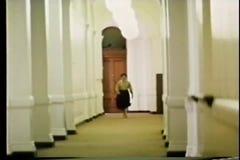 Long shot woman in a hurry walking down long hallway stock footage