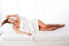 Long shot of woman lying in bed Stock Photos