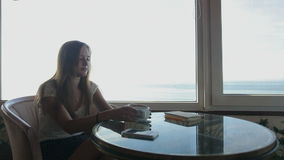Long shot of  young beautiful girl sits in a cafe. Silhouette of young beautiful woman sits in a cafe with panoramic views of sea. Morning breakfast with a cup stock video footage