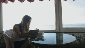Long shot of young beautiful girl sits in a cafe. Silhouette of young beautiful woman sits in a cafe with panoramic views of sea. Morning with a cup of coffe stock footage