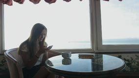 Long shot of of young beautiful girl sits in a. Silhouette of young beautiful woman sits in a cafe with panoramic views of atlantic ocean. Morning with a cup of stock video