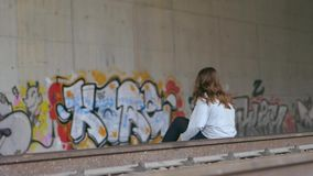 Long-shot of young Caucasian woman with brown hair sitting on the train tracks. Graffiti on tunnel walls. Slow motion. Concept of despair, depression, danger stock video