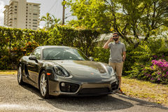 Long shot of a young man at the phone, standing by a Porsche Cay. MIAMI, USA - APRIL 30, 2016: Long shot of a young man at the phone, standing by a Porsche stock photography