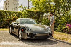 Long shot of a young man at the phone, standing by a Porsche Cay. MIAMI, USA - APRIL 30, 2016: Long shot of a young man at the phone, standing by a Porsche stock photos