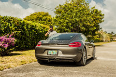 Long shot of a young man at the phone, standing by a Porsche Cay. MIAMI, USA - APRIL 30, 2016: Long shot of a young man at the phone, standing by a Porsche stock photo