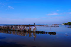 Long simple wooden jetty leading into blue ocean with sunset Stock Images