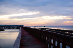 Long simple wooden jetty leading into blue ocean with sunset Royalty Free Stock Photography