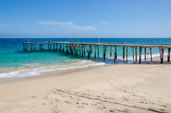 Long simple wooden jetty leading into turquoise blue ocean in Angola Stock Images