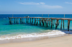 Long simple wooden jetty leading into turquoise blue ocean in Angola Royalty Free Stock Images