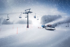 Long ski lift line and the working snow cannon on Austrian Alps Stock Images