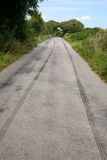 Long skid marks. Long skid marks left by a speeding car braking on a country road Royalty Free Stock Image