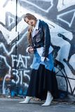 Slim trendy model wearing long baggy denim and black skirt. Long skirt. Slim trendy model wearing long baggy denim and black skirt while standing near the wall stock images
