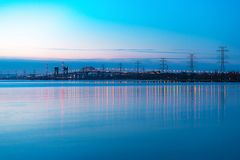 Long skyway and lift bridge aglow with lights reflecting in blue. Waters in early morning hours. Pastel sunrise colors. Space for text Stock Photos