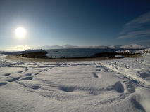 Long snowy field with footprints with beautiful bay, blue fjord and sky on a sunny winter day Royalty Free Stock Photos