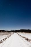 Long snowy road and clear starry sky in moon light Stock Image