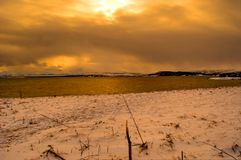 Long snowy sea shore in the arctic circle wintertime during golden sunset over snowy mountain peaks. Coloring the langscape golden Stock Photos