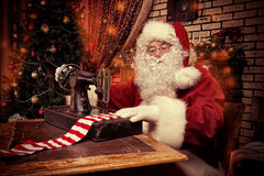 Long socks. Santa Claus is sewing on a sewing machine striped socks for Christmas Royalty Free Stock Images
