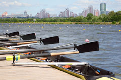 Long sport boat with oars. Stands at wooden pier at background of urban landscape. Focus on oars Royalty Free Stock Image