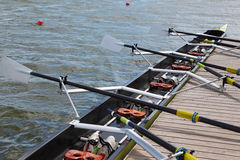 Long sport boat with oars stands. At wooden pier at sunny day Stock Photo