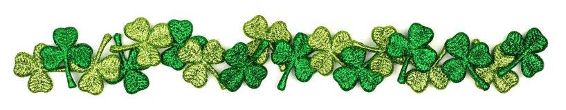 Long St Patricks Day shiny shamrocks border over white stock image