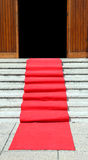 Long staircase with a luxurious red carpet toward the open door Royalty Free Stock Photo