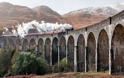 Steam train on an arched bridge to Hogwarts in the mountains royalty free stock photography