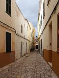 Long straight cobbled picturesque empty narrow street of old houses in cuitadella menorca royalty free stock image