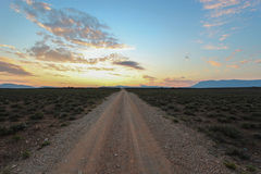 Long straight dirt road at sunset in Camdeboo National Park Royalty Free Stock Photo